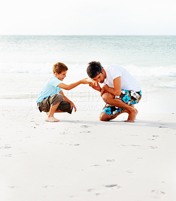 Buy stock photo Father and son at the sea shore listening to a seashell