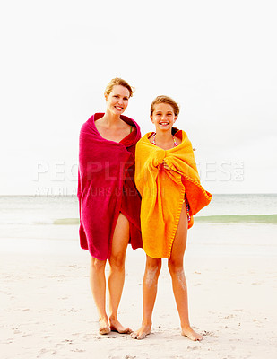 Buy stock photo Happy mother and daughter standing at the beach wrapped in a towel