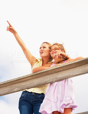 Buy stock photo Upward view of a cute woman pointing away standing with daughter by a wooden railing