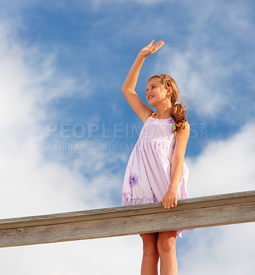Buy stock photo Upward view of a teenage girl standing on a wooden railing with a hand raised against a clouded sky