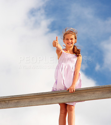 Buy stock photo Portrait of a happy teenage girl standing on a wooden railing showing a thumbs up sign outdoors