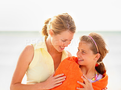 Buy stock photo Happy mother wiping her teenaged daughter dry with a towel after a swim