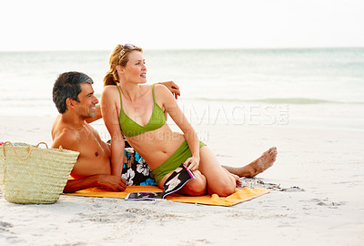 Buy stock photo Happy cute couple in swimwear relaxing at the beach, looking away