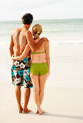 Buy stock photo Rear view of a romantic couple standing on the sea shore facing the ocean