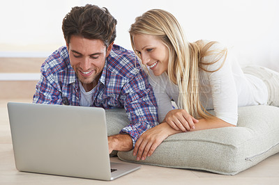 Buy stock photo A happy young couple lying on the floor at home and using a laptop together