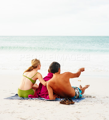 Buy stock photo Rear view of a father, mother and son sitting on the sea shore, man pointing towards the ocean