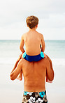 Rear view of a father carrying his son on the shoulders while on the beach