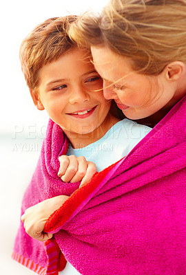 Buy stock photo Cute small boy being embraced by mother while on the beach, looking at eachother