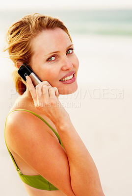 Buy stock photo Portrait of a happy young woman speaking on the cellphone while at the beach