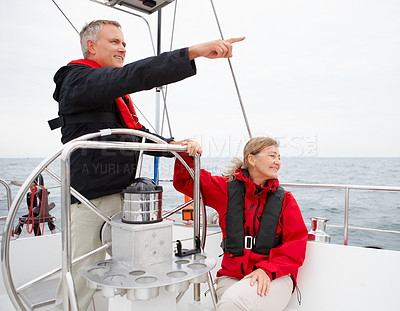 Buy stock photo Happy retired couple steering a boat on their voyage, pointing away