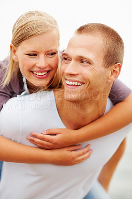 Buy stock photo Closeup of a happy young male piggybacking his girlfriend, outdoors