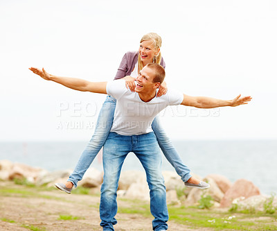 Buy stock photo Happy young couple enjoying themselves outdoors, female being piggybacked