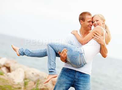 Buy stock photo Handsome young man carrying his girlfriend outdoors