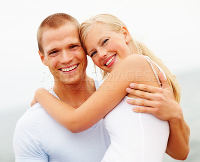 Buy stock photo Cute young couple smiling outdoors, man carrying female in his arms