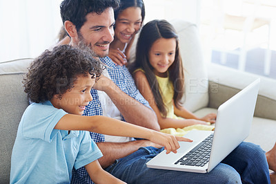 Buy stock photo Shot of a smiling family sitting on the sofa and using a laptop
