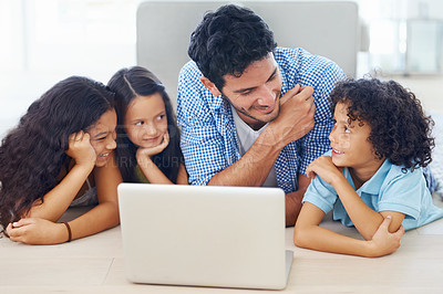 Buy stock photo Shot of a smiling family lying on the floor and surfing the internet