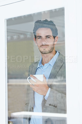Buy stock photo Portrait of a handsome young man drinking coffee while staring out of a window