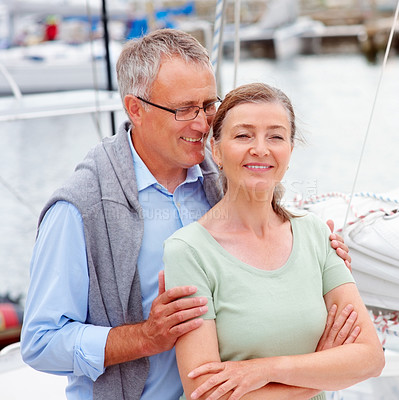 Buy stock photo Happy retired man whispering into wife's ears while on a sailboat