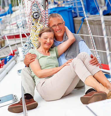 Buy stock photo Happy romantic elderly couple sitting comfortably on a sailboat