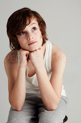 Buy stock photo A young boy resting his head in his hands while looking away