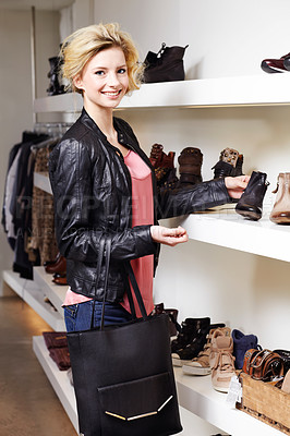 Buy stock photo Shot of an attractive and stylish young woman looking at shoes in a clothing store