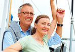 Happy retired couple while on a sea voyage on a sailboat