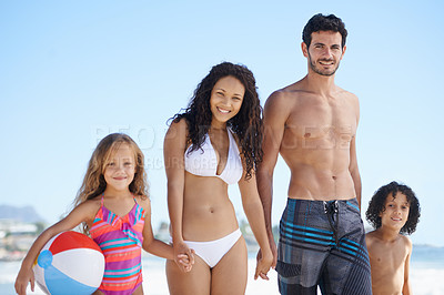 Buy stock photo A family of four walking along the beach together