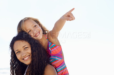 Buy stock photo A young mother piggybacking her little girl while she's pointing at something in the distance
