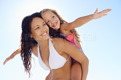 Buy stock photo A young mother carrying her daughter on her back on the beach while they both stretch out their arms
