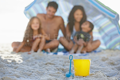 Buy stock photo A happy family smiling while sitting under an umbrella at the beach with a spade and bucket in the foreground