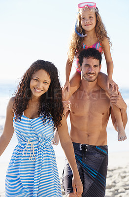 Buy stock photo A handsome young father carrying his daughter on his shoulders with his wife walking alongside him on the beach