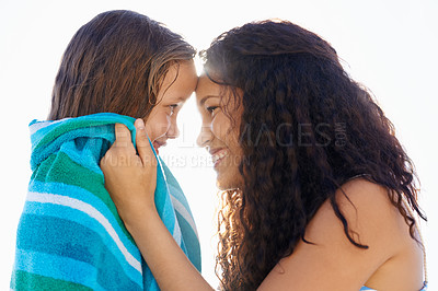 Buy stock photo A loving mother wrapping her daughter in a towel at the beach