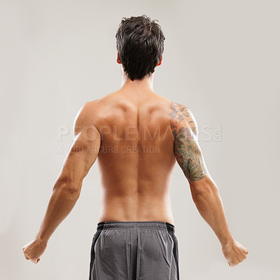 Buy stock photo Rearview of a shirtless man stretching his back before a workout