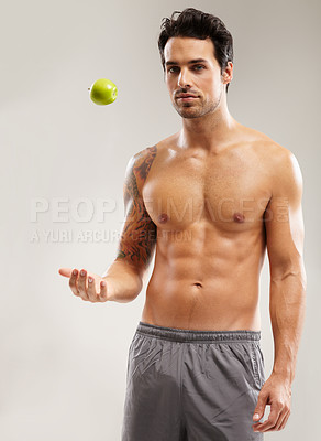 Buy stock photo Portrait of a macho young man throwing an apple in the air