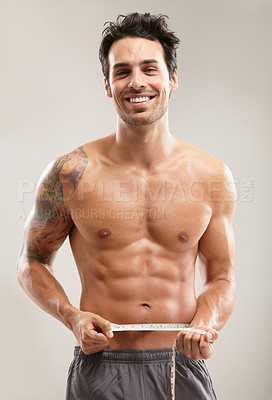 Buy stock photo Portrait of a hunky young man measuring his waist