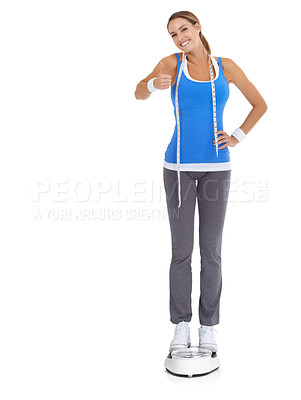 Buy stock photo Fit young woman giving you a thumb's up against a white background while standing on a scale