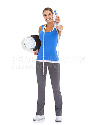 Buy stock photo Fit young woman holding a water bottle and a scale with a tape measure around her neck - isolated on white
