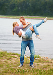 Young guy carrying his girlfriend in his arms, outdoor by the lake