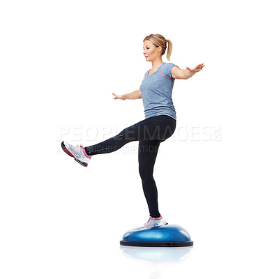 Buy stock photo An attractive young woman working her core muscles by balancing on a bosu-ball