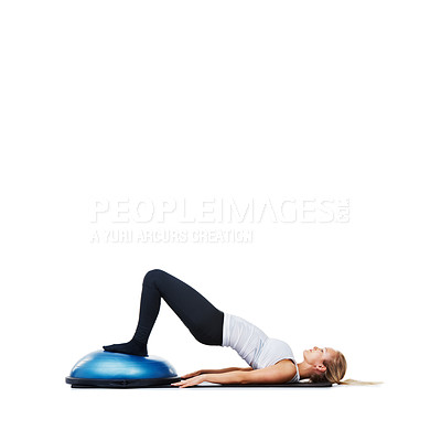 Buy stock photo An attractive young woman stretching out using a bosu-ball