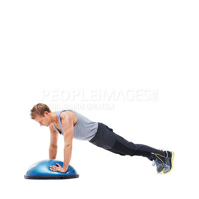 Buy stock photo A young man doing push-ups on a bosu-ball