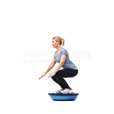 Buy stock photo An attractive young woman working out with the aid of a bosu-ball
