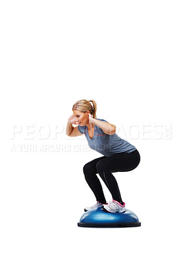 Buy stock photo A young woman standing on a bosu-ball while working out
