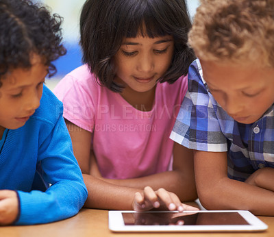 Buy stock photo Three learners working on a digital tablet while sitting in class