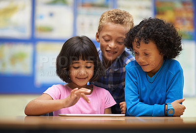 Buy stock photo Three school students working on a digital tablet in class