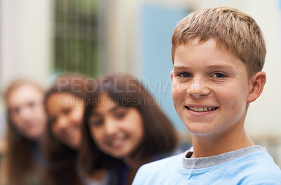 Buy stock photo Portrait of a young school boy standing with his friends blurred in the background