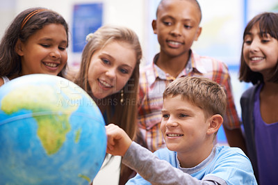 Buy stock photo A group of pupils looking at a globe during geography class