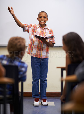Buy stock photo A young boy doing prepared reading at the front of the class