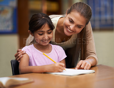 Buy stock photo Shot of a teacher helping her student with her work in the classroom