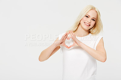 Buy stock photo A beautiful young woman making a heart shape with her fingers